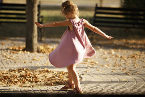Full length portrait of little girl dancing in the park